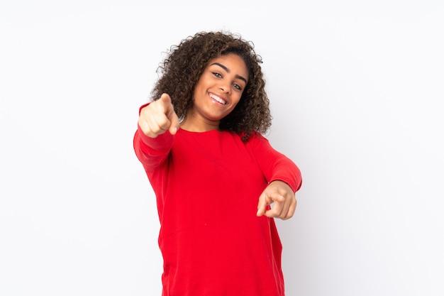 Giovane donna isolata sulla parete che indica parte anteriore con l'espressione felice