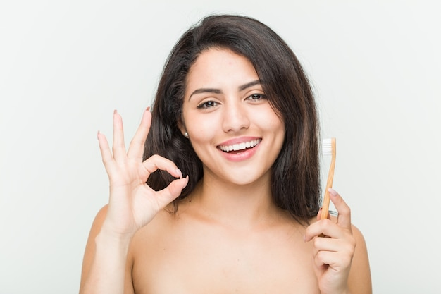Giovane donna ispanica che giudica uno spazzolino da denti allegro e sicuro che mostra gesto giusto.