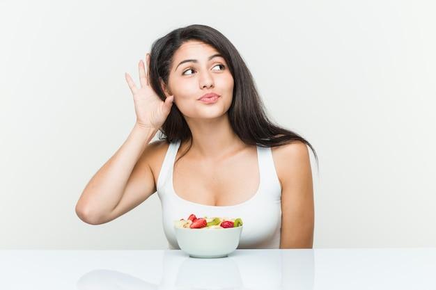 Giovane donna ispanica che mangia una ciotola di frutta che prova ad ascoltare un gossip.