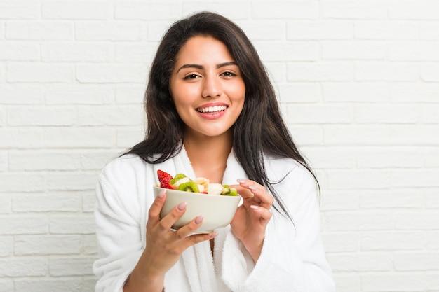 Giovane donna ispanica che mangia una ciotola di frutta sul letto