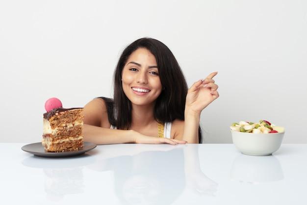 Giovane donna ispanica che sceglie fra il dolce o la frutta che sorride allegramente indicando con l'indice via.