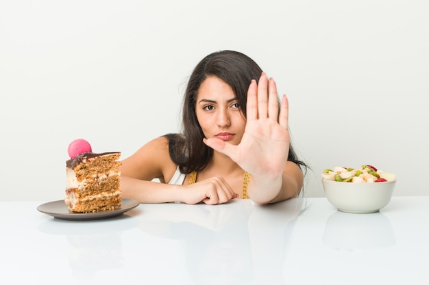 Giovane donna ispanica che sceglie fra il dolce o la frutta che sta con il fanale di arresto di rappresentazione della mano tesa, impedendovi.