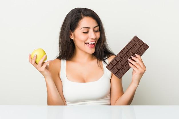 Giovane donna ispanica che sceglie fra la compressa del cioccolato o della mela