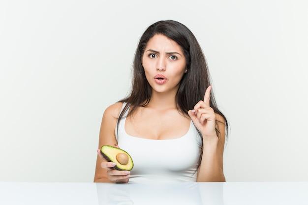 Giovane donna ispanica che tiene un avocado che ha una grande idea, concetto di creatività.
