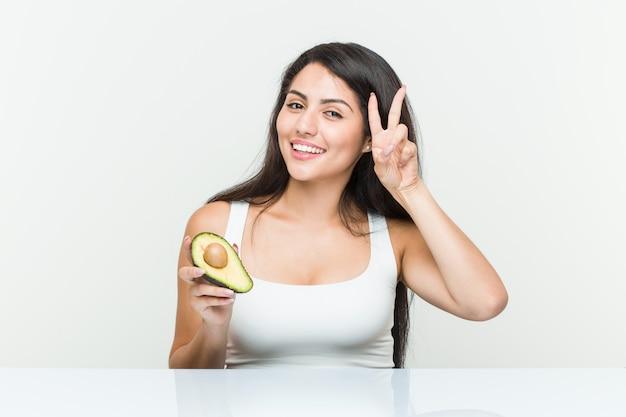 Giovane donna ispanica che tiene un avocado che mostra il segno di vittoria e che sorride ampiamente.