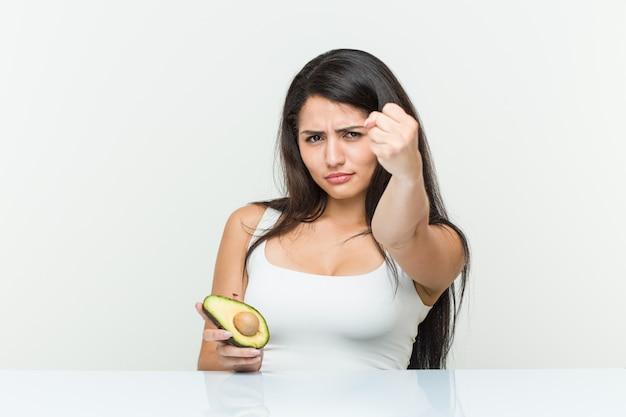 Giovane donna ispanica che tiene un avocado che mostra pugno alla macchina fotografica, espressione facciale aggressiva.