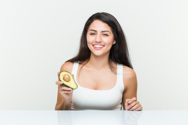 Giovane donna ispanica che tiene un avocado che sorride e che alza pollice in su