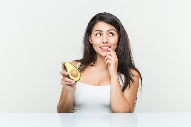Giovane donna ispanica che tiene un avocado rilassato pensando a qualcosa