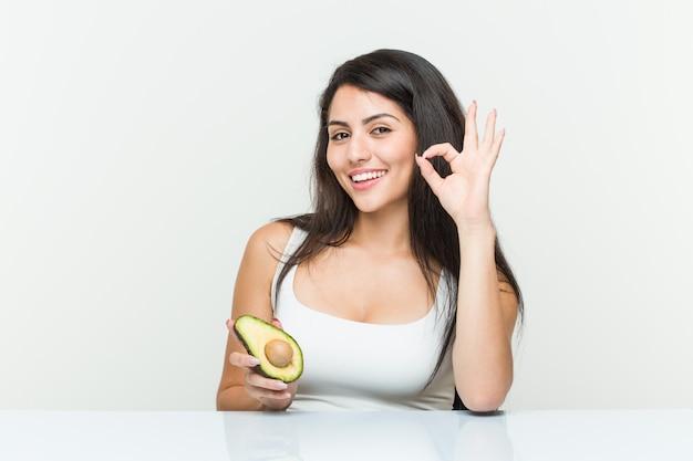 Giovane donna ispanica che tiene un gesto giusto di mostra allegro e sicuro di avocado.