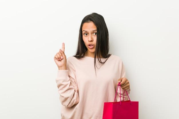 Giovane donna ispanica che tiene un sacchetto della spesa che ha una certa grande idea, concetto di creatività.