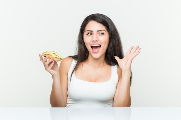 Giovane donna ispanica che tiene un toast di avocado che celebra una vittoria o un successo