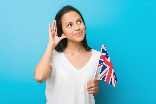 Giovane donna ispanica che tiene una bandiera del regno unito che prova ad ascoltare un gossip.