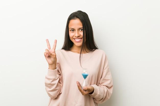 Giovane donna ispanica che tiene una clessidra che mostra numero due con le dita.
