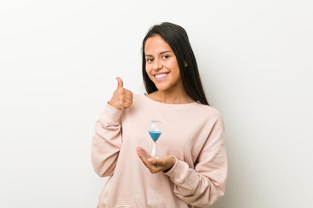 Giovane donna ispanica che tiene una clessidra che sorride e che alza pollice in su