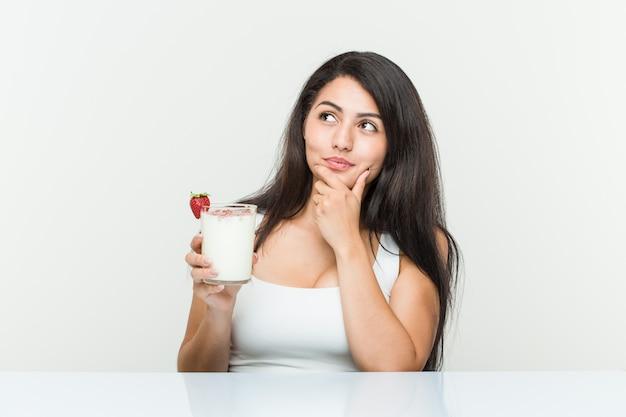 Giovane donna ispanica con in mano un frullato giovane donna ispanica con in mano un brindisi con avocado che guarda lateralmente con espressione dubbiosa e scettica. <mixto>