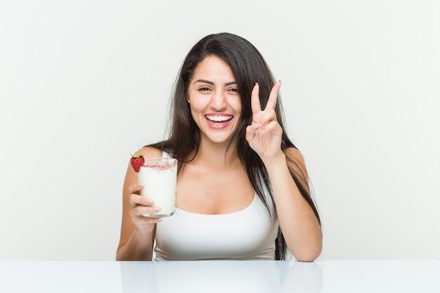 Giovane donna ispanica con in mano un frullato giovane donna ispanica con in mano un brindisi con avocado che mostra il numero due con le dita. <mixto>