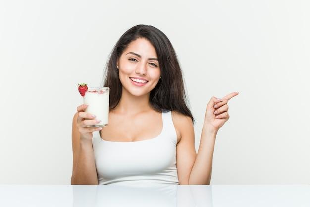 Giovane donna ispanica con in mano un frullato giovane donna ispanica con in mano un brindisi con avocado che sorride allegramente indicando con l'indice di distanza