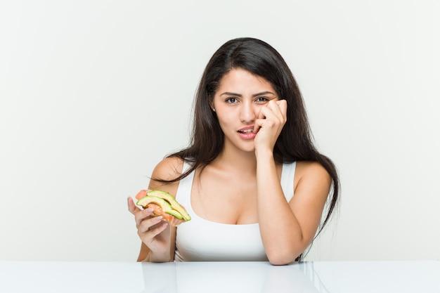 Giovane donna ispanica con in mano un toast di avocado che morde le unghie, nervosa e molto ansiosa.