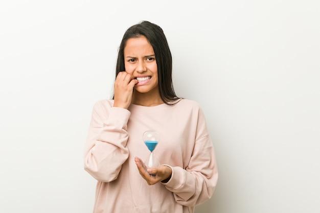 Giovane donna ispanica con in mano una clessidra che morde le unghie, nervosa e molto ansiosa.