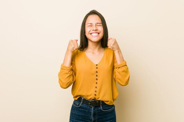 Giovane donna ispanica contro un muro beige alzando il pugno, sentendosi felice e di successo. concetto di vittoria.