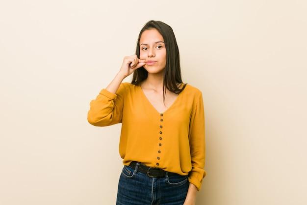 Giovane donna ispanica contro un muro beige con le dita sulle labbra mantenendo un segreto.