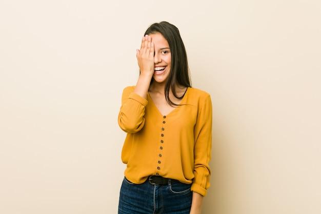 Giovane donna ispanica contro un muro beige divertirsi coprendo metà del viso con il palmo.
