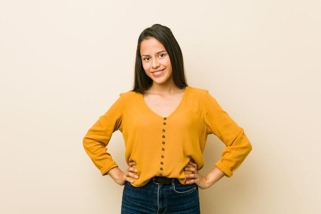 Giovane donna ispanica contro un muro beige fiducioso mantenendo le mani sui fianchi.