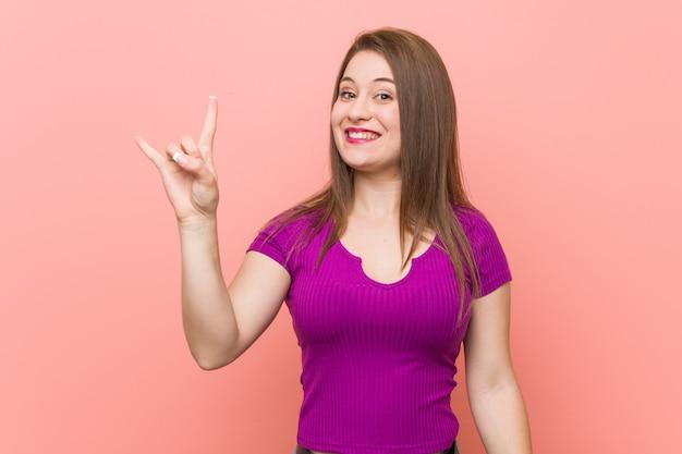 Giovane donna ispanica contro un muro rosa che mostra un gesto di corna come una rivoluzione.