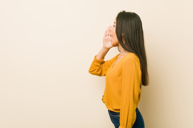 Giovane donna ispanica contro una parete beige che grida e che tiene il palmo vicino alla bocca aperta.
