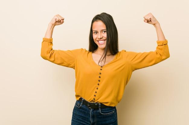 Giovane donna ispanica contro una parete beige che mostra il gesto di forza con le braccia, simbolo del potere femminile