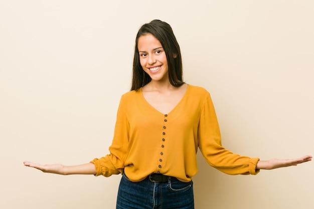 Giovane donna ispanica contro una parete beige che mostra un'espressione benvenuta.