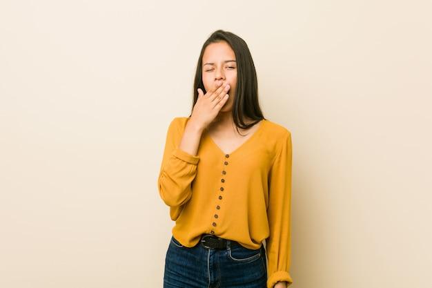 Giovane donna ispanica contro una parete beige che sbadiglia mostrando un gesto stanco che copre la bocca con la mano.