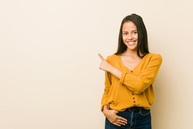 Giovane donna ispanica contro una parete beige che sorride e che indica da parte, mostrando qualcosa nello spazio.