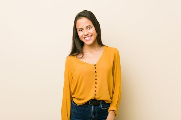 Giovane donna ispanica contro una parete beige felice, sorridente e allegra.