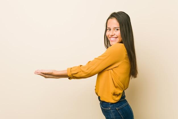 Giovane donna ispanica contro una parete beige in possesso di uno spazio di copia su una palma.
