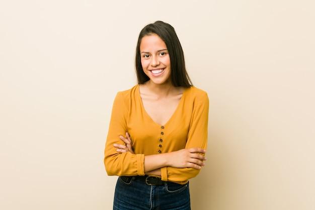 Giovane donna ispanica contro una parete beige ridendo e divertendosi.