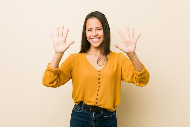 Giovane donna ispanica contro uno sfondo beige che mostra il numero dieci con le mani