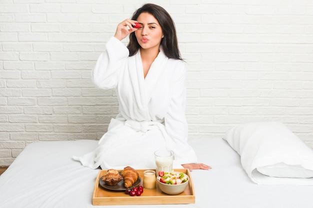 Giovane donna ispanica facendo colazione sul letto