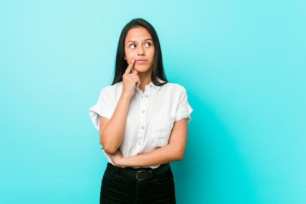 Giovane donna ispanica fresca contro una parete blu guardando lateralmente con espressione dubbiosa e scettica.
