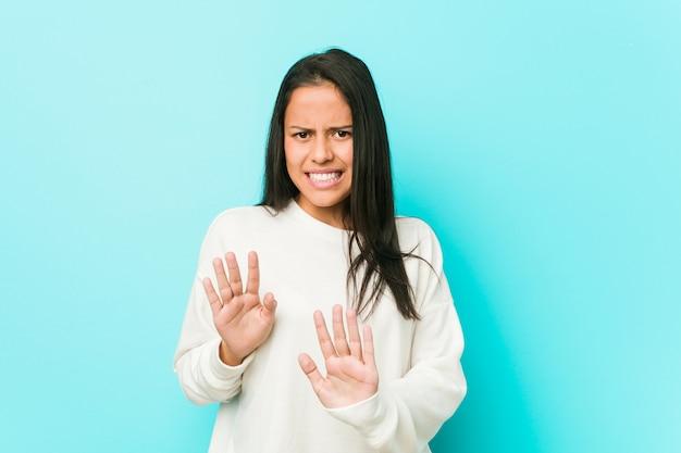 Giovane donna ispanica graziosa che rifiuta qualcuno che mostra un gesto di disgusto.