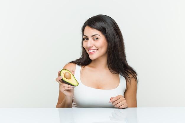 Giovane donna ispanica in possesso di un avocado felice, sorridente e allegro.