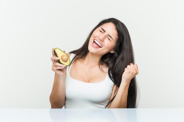 Giovane donna ispanica in possesso di un avocado tifo spensierato ed eccitato
