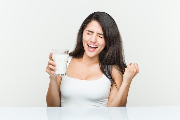 Giovane donna ispanica in possesso di un bicchiere di latte tifo spensierato ed eccitato. concetto di vittoria.