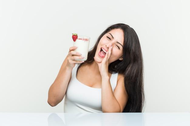 Giovane donna ispanica in possesso di un frullato giovane donna ispanica in possesso di un brindisi di avocado gridando eccitato al fronte.