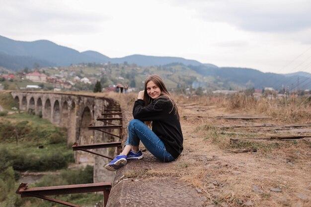 Giovane donna itinerante con zaino seduto in alto sulla cima della montagna con agitando i capelli