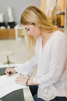 Giovane donna laterale che abbozza sulla carta con la matita sul banco da lavoro