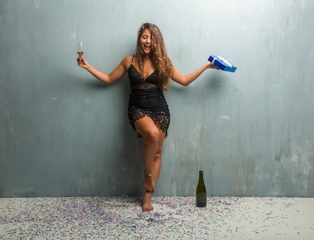 Giovane donna latina che celebra un nuovo anno o un evento, bevendo champagne, a piedi nudi e in possesso di un regalo blu.