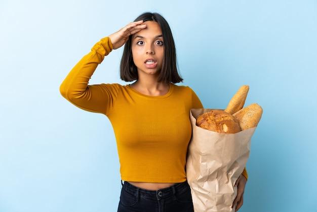 Giovane donna latina che compra alcuni pani isolati sul blu con l'espressione di sorpresa