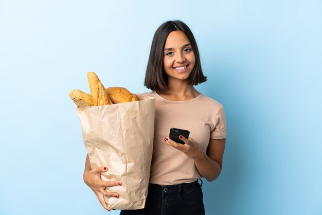 Giovane donna latina che compra alcuni pani isolati sull'azzurro che invia un messaggio con il cellulare