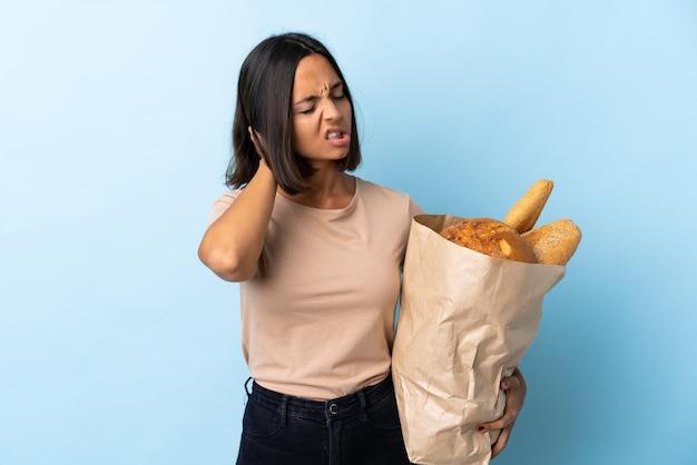 Giovane donna latina che compra alcuni pani isolati sull'azzurro con il mal di collo